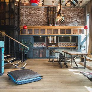 Imagen de cocina lineal, industrial, grande, abierta, sin isla, con puertas de armario azules y suelo de madera clara