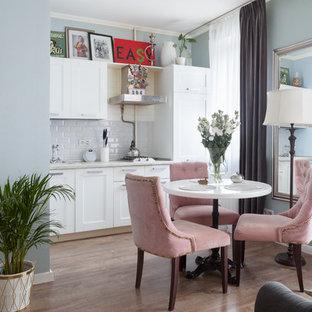 Пример оригинального дизайна: линейная кухня-гостиная в современном стиле с накладной раковиной, фасадами в стиле шейкер, белыми фасадами, белым фартуком, фартуком из плитки кабанчик, полом из ламината и коричневым полом без острова