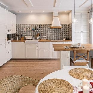 Idéer för att renovera ett nordiskt kök, med en rustik diskho, vita skåp, flerfärgad stänkskydd, vita vitvaror, ljust trägolv och en halv köksö