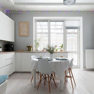 Неиссякаемый источник вдохновения для домашнего уюта: угловая кухня-гостиная в современном стиле с плоскими фасадами, белыми фасадами, серым фартуком, белой техникой, светлым паркетным полом и бежевым полом без острова