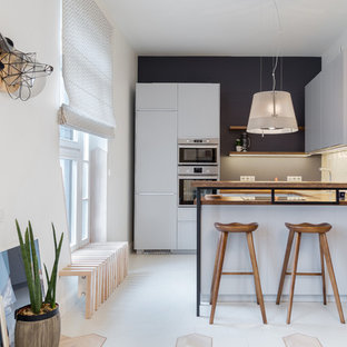 На фото: маленькая п-образная кухня-гостиная в скандинавском стиле с накладной раковиной, плоскими фасадами, серыми фасадами, деревянной столешницей, бежевым фартуком, фартуком из плитки мозаики, техникой из нержавеющей стали, полом из керамической плитки, полуостровом и бежевым полом с