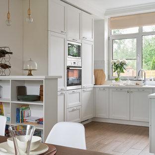Новый формат декора квартиры: п-образная кухня в стиле современная классика с врезной раковиной, фасадами с утопленной филенкой, белыми фасадами, белым фартуком, техникой из нержавеющей стали, паркетным полом среднего тона, коричневым полом и белой столешницей