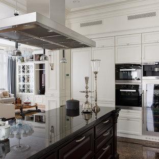 На фото: кухня-гостиная среднего размера в стиле современная классика с мраморным полом, коричневым полом, белыми фасадами, островом, фасадами с утопленной филенкой и черной техникой