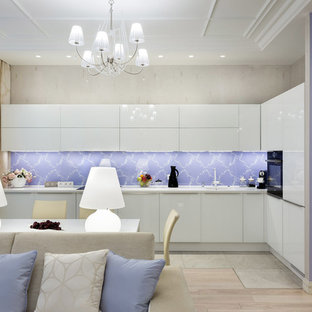 Inspiration for a mid-sized contemporary l-shaped open plan kitchen in Saint Petersburg with an integrated sink, flat-panel cabinets, white cabinets, glass sheet splashback, black appliances, no island, solid surface benchtops, multi-coloured splashback, ceramic floors, grey floor and white benchtop.