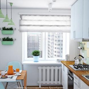 サンクトペテルブルクの小さい北欧スタイルのおしゃれなキッチン (ドロップインシンク、フラットパネル扉のキャビネット、白いキャビネット、木材カウンター、マルチカラーのキッチンパネル、セラミックタイルのキッチンパネル、シルバーの調理設備、無垢フローリング、アイランドなし、茶色い床、茶色いキッチンカウンター) の写真