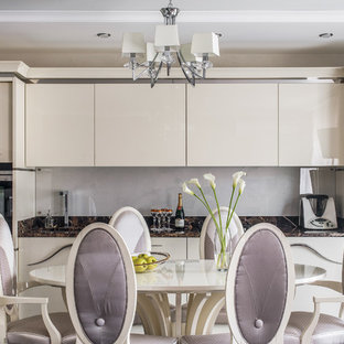 Design ideas for a contemporary single-wall eat-in kitchen in Other with an undermount sink, flat-panel cabinets, beige cabinets, grey splashback, glass sheet splashback, panelled appliances and brown benchtop.