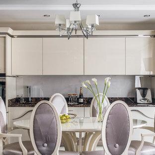 Пример оригинального дизайна: линейная кухня в современном стиле с врезной раковиной, плоскими фасадами, бежевыми фасадами, обеденным столом, серым фартуком, фартуком из стекла, техникой под мебельный фасад и коричневой столешницей
