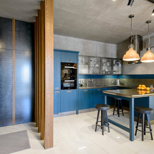 Inspiration for an industrial u-shaped open plan kitchen in Novosibirsk with flat-panel cabinets, blue cabinets, stainless steel benchtops, grey splashback, metal splashback, a peninsula, grey benchtop, an undermount sink, panelled appliances and beige floor.