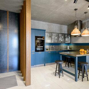 Новый формат декора квартиры: п-образная кухня-гостиная в стиле лофт с плоскими фасадами, синими фасадами, столешницей из нержавеющей стали, серым фартуком, фартуком из металлической плитки, полуостровом, серой столешницей, врезной раковиной, техникой под мебельный фасад и бежевым полом