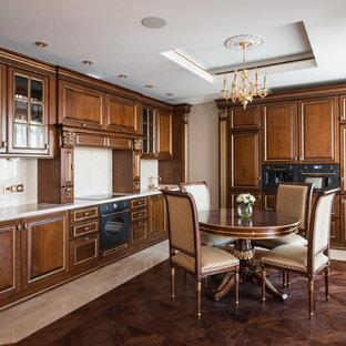 Свежая идея для дизайна: большая угловая кухня в классическом стиле с обеденным столом, фасадами с выступающей филенкой, мраморной столешницей, бежевым фартуком, черной техникой, темным паркетным полом и фасадами цвета дерева среднего тона без острова - отличное фото интерьера