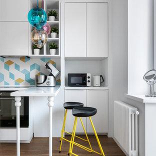 Пример оригинального дизайна: отдельная, прямая кухня в современном стиле с плоскими фасадами, белыми фасадами, разноцветным фартуком, фартуком из цементной плитки, черной техникой, паркетным полом среднего тона, полуостровом, белой столешницей, коричневым полом и барной стойкой