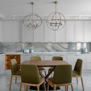 Пример оригинального дизайна: угловая кухня среднего размера в современном стиле с обеденным столом, накладной раковиной, фасадами с утопленной филенкой, белыми фасадами, серым фартуком, техникой из нержавеющей стали, серым полом и белой столешницей без острова