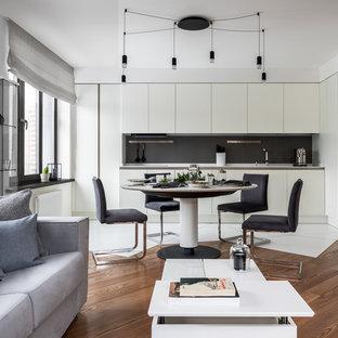 Пример оригинального дизайна: большая угловая кухня-гостиная в современном стиле с врезной раковиной, плоскими фасадами, белыми фасадами, серым фартуком, белой техникой, полом из керамической плитки, белым полом и белой столешницей без острова