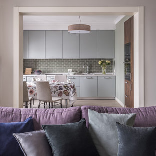 Design ideas for a mid-sized transitional single-wall open plan kitchen in Moscow with flat-panel cabinets, green cabinets, quartz benchtops, green splashback, ceramic splashback, light hardwood floors, no island, an integrated sink, black appliances, beige floor and beige benchtop.