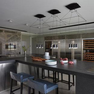 На фото: кухня в современном стиле с плоскими фасадами, техникой из нержавеющей стали, островом и серой столешницей
