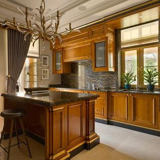 На фото: кухни в стиле современная классика с врезной раковиной, фасадами цвета дерева среднего тона, черным фартуком, островом и бежевым полом