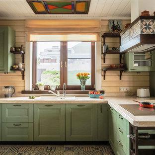 На фото: п-образные кухни в стиле кантри с накладной раковиной, зелеными фасадами, бежевым фартуком, белой техникой, полуостровом, разноцветным полом, фасадами с утопленной филенкой, фартуком из дерева и полом из цементной плитки