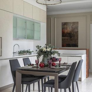 На фото: угловая кухня-гостиная среднего размера в современном стиле с монолитной раковиной, плоскими фасадами, белыми фасадами, белым фартуком, бежевым полом и полом из керамогранита без острова с