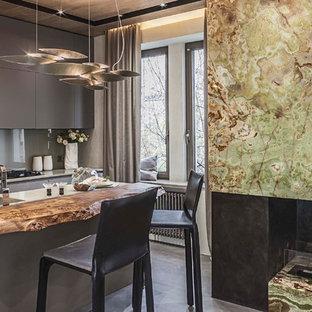 Свежая идея для дизайна: линейная кухня-гостиная среднего размера в современном стиле с монолитной раковиной, плоскими фасадами, серыми фасадами, столешницей из акрилового камня, серым фартуком, фартуком из стекла, черной техникой, полом из керамогранита и островом - отличное фото интерьера
