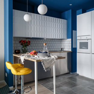 Moderne Küche in L-Form mit flächenbündigen Schrankfronten, weißen Schränken, Arbeitsplatte aus Holz, Küchenrückwand in Weiß, weißen Elektrogeräten, Halbinsel, grauem Boden und brauner Arbeitsplatte in Moskau