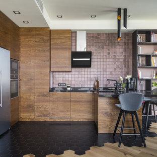 Новый формат декора квартиры: п-образная кухня в современном стиле с врезной раковиной, плоскими фасадами, фасадами цвета дерева среднего тона, розовым фартуком, черной техникой, полуостровом, черным полом и черной столешницей