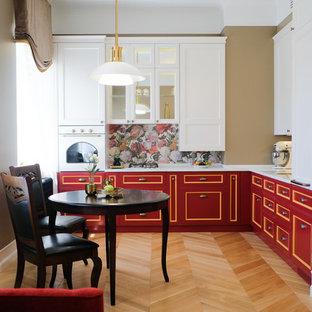 Источник вдохновения для домашнего уюта: маленькая угловая кухня в классическом стиле с обеденным столом, красными фасадами, столешницей из акрилового камня, разноцветным фартуком, белой техникой, паркетным полом среднего тона, белой столешницей, врезной раковиной, коричневым полом и фасадами с утопленной филенкой без острова