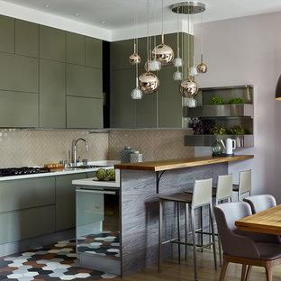 Создайте стильный интерьер: п-образная кухня среднего размера в современном стиле с обеденным столом, одинарной раковиной, плоскими фасадами, зелеными фасадами, столешницей из акрилового камня, фартуком из керамической плитки, полом из керамогранита, разноцветным полом, белой столешницей, бежевым фартуком, черной техникой и полуостровом - последний тренд