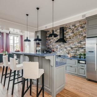 Свежая идея для дизайна: большая параллельная кухня в стиле фьюжн с обеденным столом, раковиной в стиле кантри, фасадами с выступающей филенкой, серыми фасадами, столешницей из акрилового камня, синим фартуком, фартуком из керамической плитки, техникой под мебельный фасад, полом из керамогранита, островом, коричневым полом и синей столешницей - отличное фото интерьера