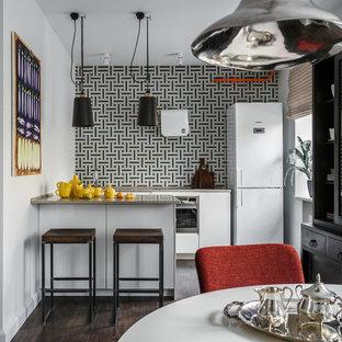 На фото: прямая кухня в современном стиле с обеденным столом, плоскими фасадами, белыми фасадами, разноцветным фартуком, белой техникой, темным паркетным полом, полуостровом, коричневым полом и серой столешницей