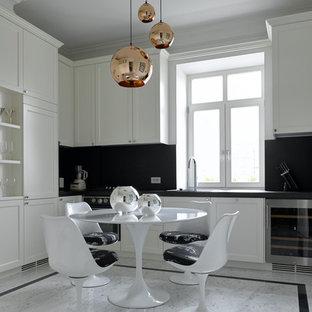 Идея дизайна: угловая кухня в современном стиле с фасадами с утопленной филенкой, белыми фасадами, черным фартуком, серым полом и черной столешницей без острова