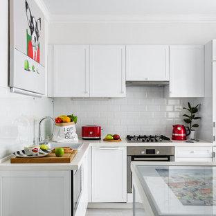 Свежая идея для дизайна: угловая кухня в современном стиле с накладной раковиной, белыми фасадами, белым фартуком, фартуком из плитки кабанчик, техникой под мебельный фасад, островом, серым полом, белой столешницей и фасадами с утопленной филенкой - отличное фото интерьера