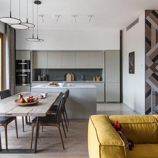 Стильный дизайн: прямая кухня-гостиная в современном стиле с светлым паркетным полом, бежевым полом, врезной раковиной, плоскими фасадами, серыми фасадами, серым фартуком, техникой из нержавеющей стали и островом - последний тренд