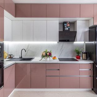 Свежая идея для дизайна: угловая кухня среднего размера в современном стиле с обеденным столом, врезной раковиной, плоскими фасадами, белыми фасадами, черной техникой, серым фартуком, полом из керамогранита, бежевым полом и белой столешницей без острова - отличное фото интерьера