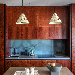 モスクワの小さいコンテンポラリースタイルのおしゃれなキッチン (シングルシンク、フラットパネル扉のキャビネット、濃色木目調キャビネット、人工大理石カウンター、緑のキッチンパネル、セラミックタイルのキッチンパネル、黒い調理設備、ラミネートの床、黒い床、ベージュのキッチンカウンター) の写真
