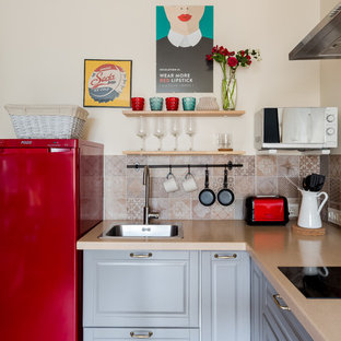 Создайте стильный интерьер: маленькая угловая кухня в стиле фьюжн с накладной раковиной, фасадами с выступающей филенкой, серыми фасадами, столешницей из акрилового камня, фартуком из керамической плитки, цветной техникой, полом из ламината, бежевой столешницей и разноцветным фартуком - последний тренд