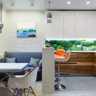 Свежая идея для дизайна: угловая кухня среднего размера в современном стиле с обеденным столом, плоскими фасадами, белыми фасадами, зеленым фартуком, полуостровом, фартуком из стекла и полом из керамической плитки - отличное фото интерьера
