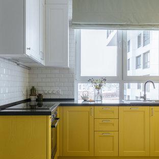 На фото: угловая кухня в стиле неоклассика (современная классика) с накладной раковиной, фасадами с утопленной филенкой, желтыми фасадами, белым фартуком, фартуком из плитки кабанчик, черной техникой, светлым паркетным полом, бежевым полом и черной столешницей с