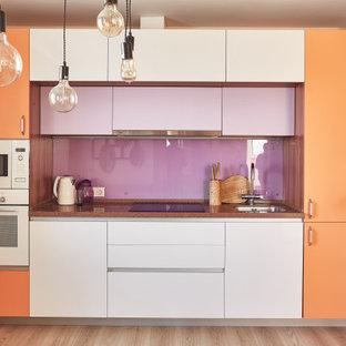 Идея дизайна: прямая кухня среднего размера в современном стиле с обеденным столом, одинарной раковиной, плоскими фасадами, оранжевыми фасадами, столешницей из акрилового камня, фартуком из стекла, белой техникой, полом из ламината, коричневым полом и коричневой столешницей без острова