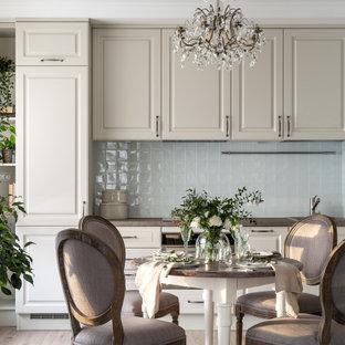 サンクトペテルブルクの中くらいのトラディショナルスタイルのおしゃれなキッチン (アンダーカウンターシンク、レイズドパネル扉のキャビネット、ベージュのキャビネット、人工大理石カウンター、青いキッチンパネル、セラミックタイルのキッチンパネル、白い調理設備、ラミネートの床、アイランドなし、ベージュの床、茶色いキッチンカウンター) の写真