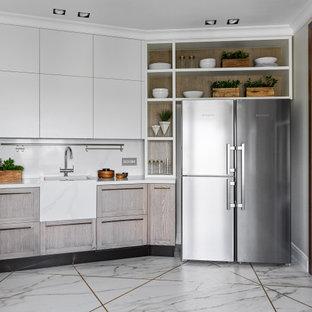 Свежая идея для дизайна: кухня в современном стиле с раковиной в стиле кантри, фасадами с утопленной филенкой, светлыми деревянными фасадами, белым фартуком, техникой из нержавеющей стали и белой столешницей без острова - отличное фото интерьера