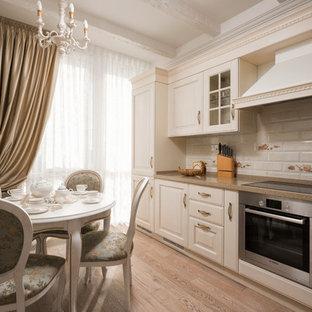Свежая идея для дизайна: отдельная, линейная кухня в классическом стиле с белыми фасадами, белым фартуком, фартуком из плитки кабанчик, техникой из нержавеющей стали, фасадами с выступающей филенкой, паркетным полом среднего тона и коричневым полом без острова - отличное фото интерьера