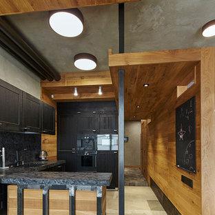 Новый формат декора квартиры: угловая кухня-гостиная среднего размера в стиле лофт с врезной раковиной, черными фасадами, столешницей из гранита, черным фартуком, фартуком из мрамора, черной техникой, полом из керамической плитки, островом, серым полом и фасадами с утопленной филенкой