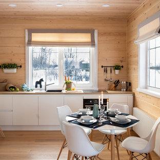 На фото: линейные кухни в скандинавском стиле с обеденным столом, накладной раковиной, плоскими фасадами, белыми фасадами, столешницей из дерева, черной техникой, паркетным полом среднего тона, коричневым полом и коричневой столешницей