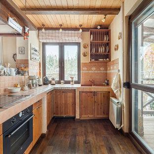 Rustik inredning av ett kök, med en nedsänkt diskho, luckor med infälld panel, skåp i mellenmörkt trä, kaklad bänkskiva, beige stänkskydd, stänkskydd i keramik, svarta vitvaror, mörkt trägolv, brunt golv och en halv köksö