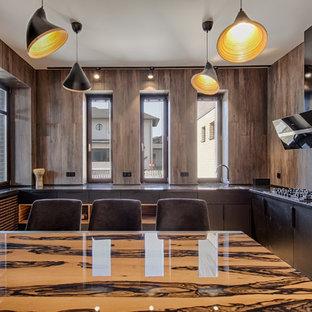 Пример оригинального дизайна: большая п-образная кухня в современном стиле с обеденным столом, плоскими фасадами, черными фасадами, серым фартуком, черной техникой и черной столешницей в частном доме