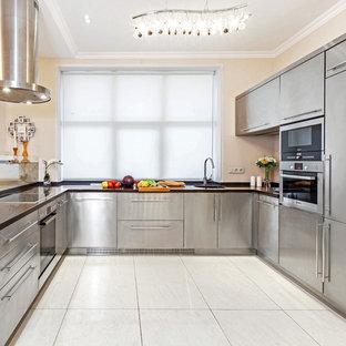 На фото: п-образная кухня в современном стиле с врезной раковиной, плоскими фасадами, кухней из нержавеющей стали, техникой из нержавеющей стали, бежевым полом и черной столешницей
