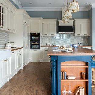 Источник вдохновения для домашнего уюта: угловая кухня в классическом стиле с раковиной в стиле кантри, фасадами с утопленной филенкой, белыми фасадами, деревянной столешницей, белым фартуком, фартуком из плитки мозаики, черной техникой, паркетным полом среднего тона, островом, коричневым полом и коричневой столешницей