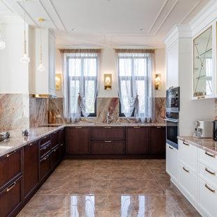 他の地域の広いトランジショナルスタイルのおしゃれなキッチン (アンダーカウンターシンク、落し込みパネル扉のキャビネット、濃色木目調キャビネット、珪岩カウンター、ピンクのキッチンパネル、大理石のキッチンパネル、シルバーの調理設備、磁器タイルの床、茶色い床、ピンクのキッチンカウンター) の写真