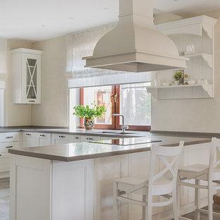 Пример оригинального дизайна: п-образная кухня в стиле неоклассика (современная классика) с обеденным столом, двойной раковиной, фасадами с утопленной филенкой, белыми фасадами, полуостровом, коричневым полом и серой столешницей в частном доме