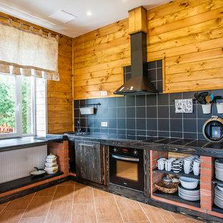サンクトペテルブルクのラスティックスタイルのおしゃれなL型キッチン (シングルシンク、オープンシェルフ、濃色木目調キャビネット、タイルカウンター、黒いキッチンパネル、黒い調理設備、アイランドなし、茶色い床) の写真
